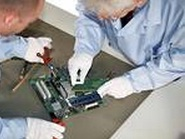 Electronics repair service technicians have circuit board on the work bench.